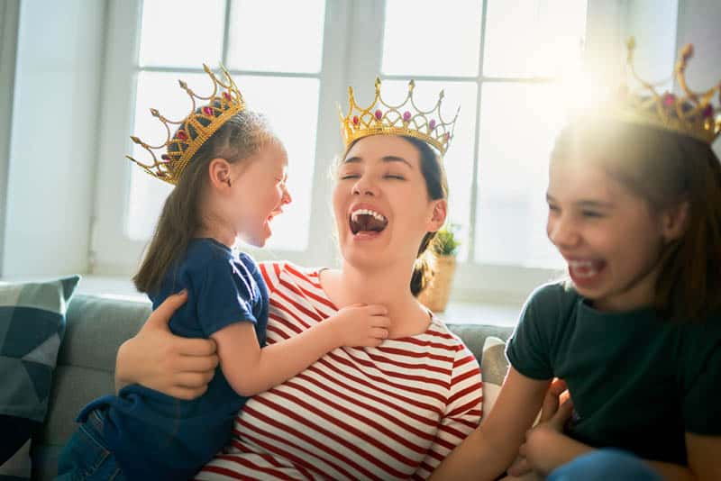 young mother playing with her daughters on the couch with crowns on their heads