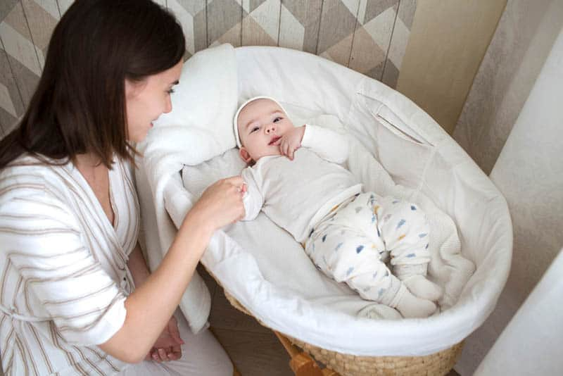 young smiling mother sitting next to baby in cradle
