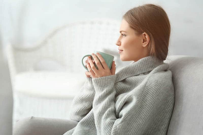 young woman drinking tea while resting in sofa