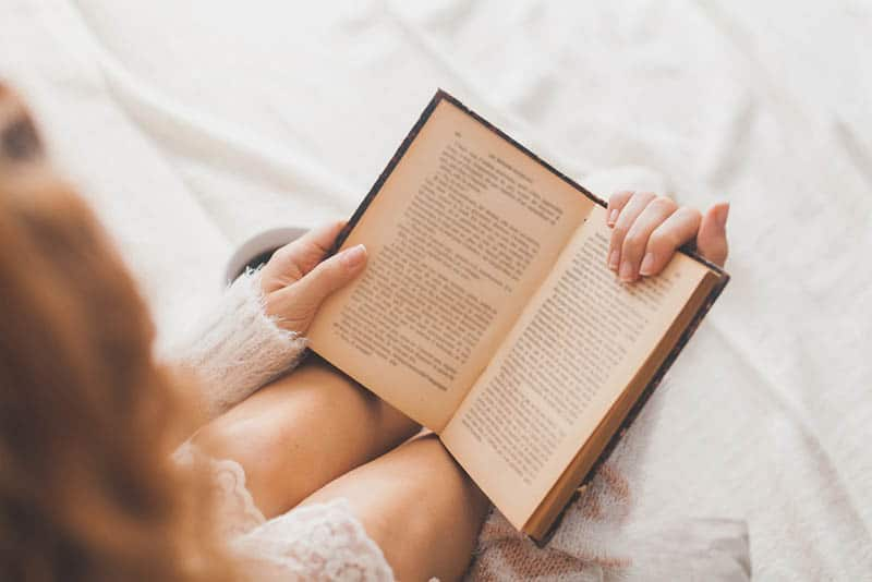 young woman in a sleeping dress reading a book in the bed