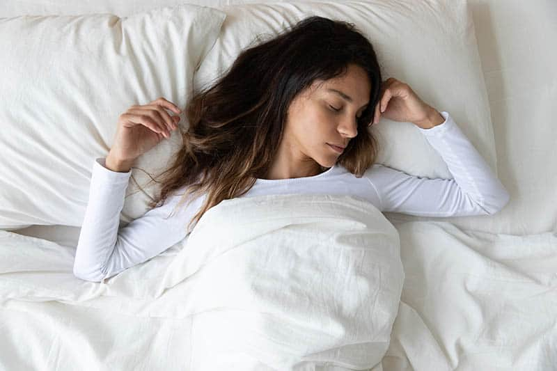 young woman sleeping in comfortable bed and dreaming