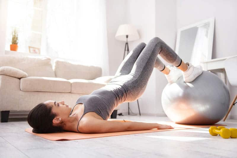 young woman working out with pilates ball on the floor at home