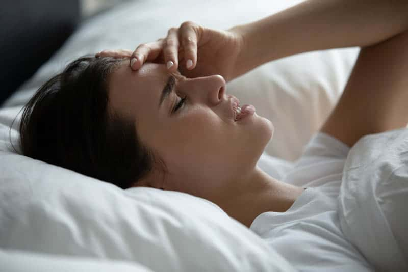 young worried woman lying in bed holding for head
