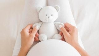 pregnant woman holding a teddy bear toy for her unborn baby in her lap