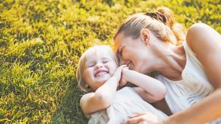 single mom and daughter laughing while laying on the grass