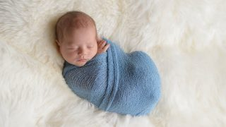 newborn baby sleeping in a blue swaddle