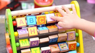 kid playing with educational toy with letters