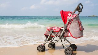 red baby beach stroller by the sea