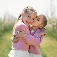 happy twin sisters hugging outside