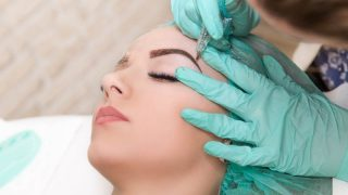 young woman getting a microblading treatment at a beauty salon