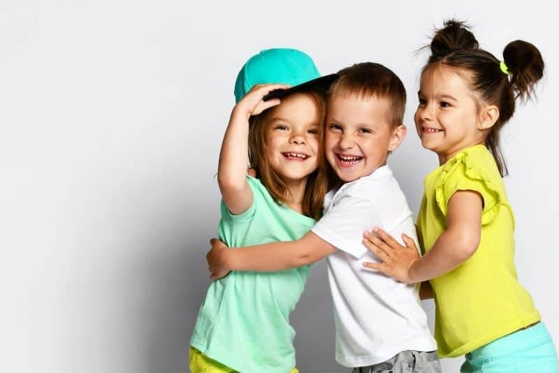 three kids hugging and smiling