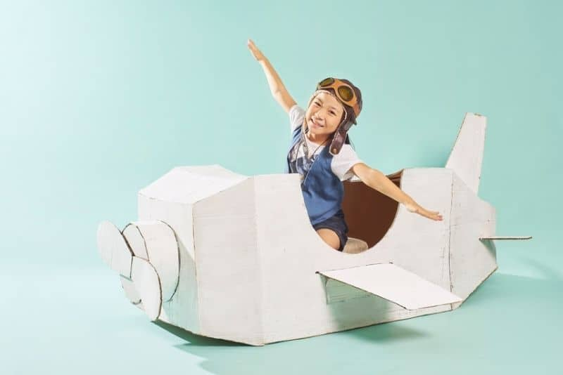 little girl pretending to fly an airplane