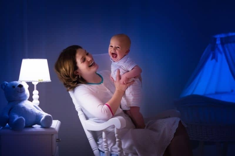 Mother holding smiling baby late at night