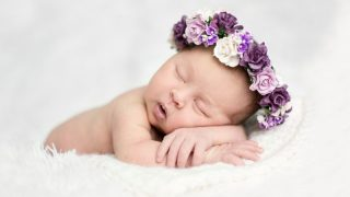 nweborn baby with a flower crown sleeping