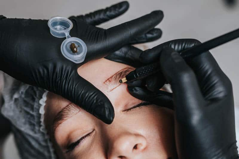Cosmetologist preparing young woman for eyebrow permanent makeup