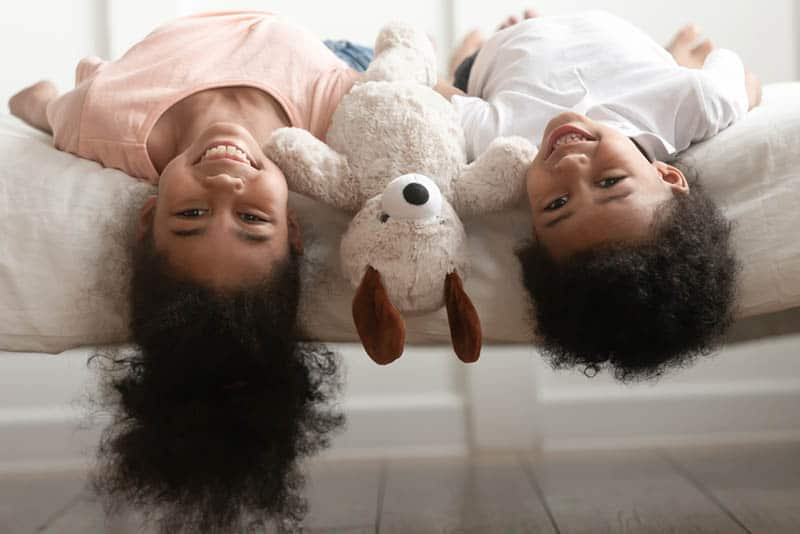 Funny cute little boy and girl laughing lying upside down on bed with toy