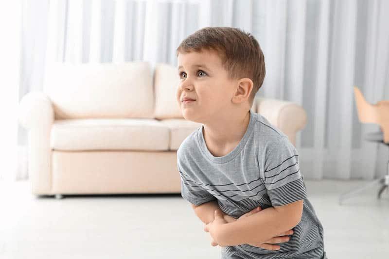 Little boy suffering from nausea in living room