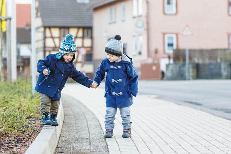 Two little sibling boys walking on the street in winter