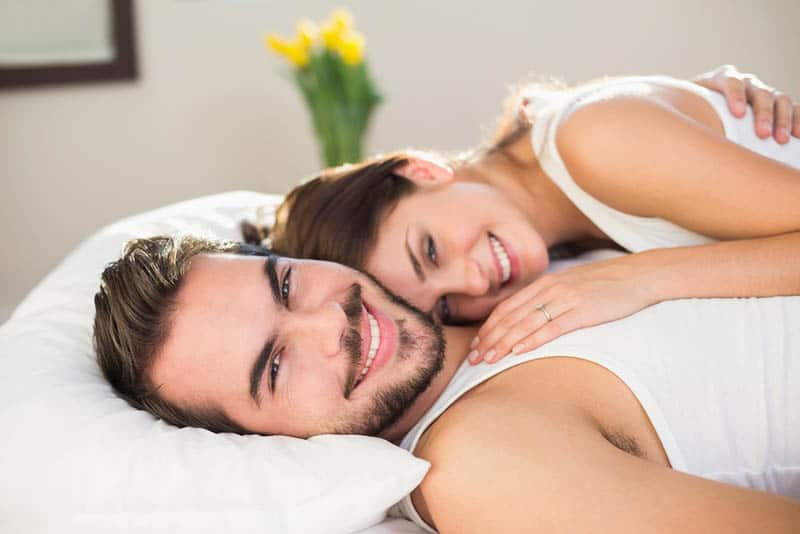Young couple cuddling in bed at home in bedroom