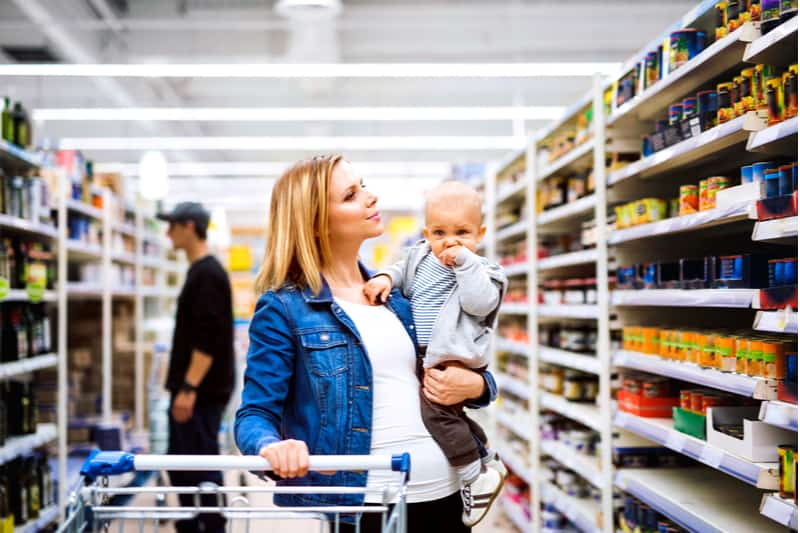 Young mother with her little baby boy at the supermarket