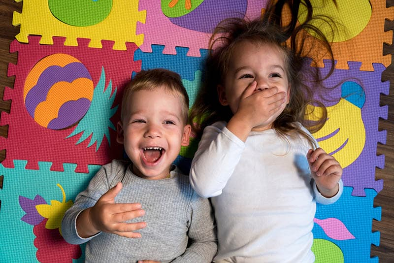 adorable baby boy laughing with sister on a playing mat