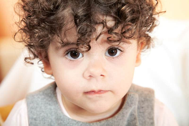 adorable baby boy with curly hair posing