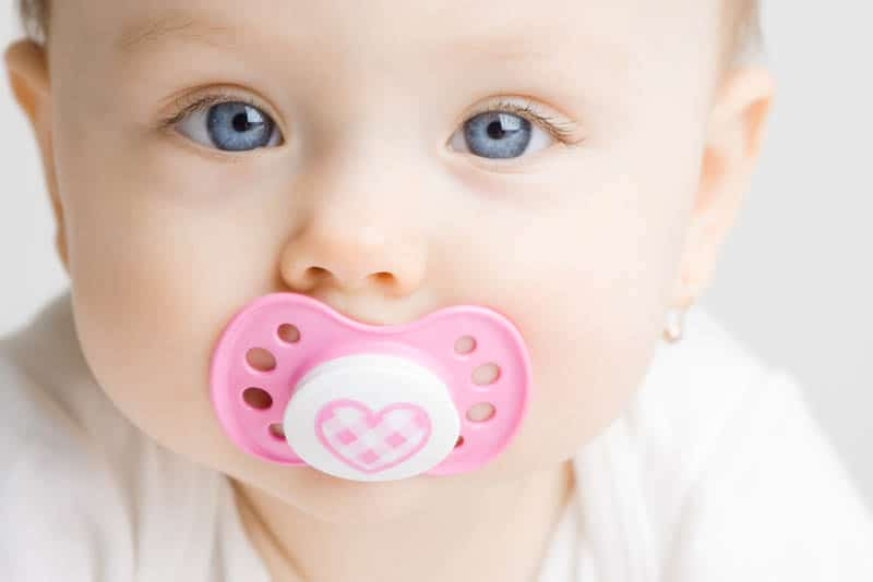 adorable baby girl with blue eyes sucking her pink pacifier