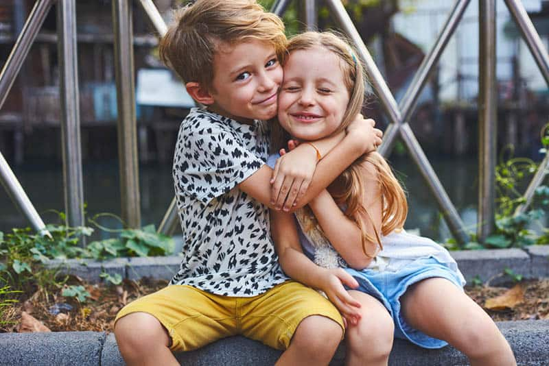 adorable little brother hugging his sister on the wall outdoor