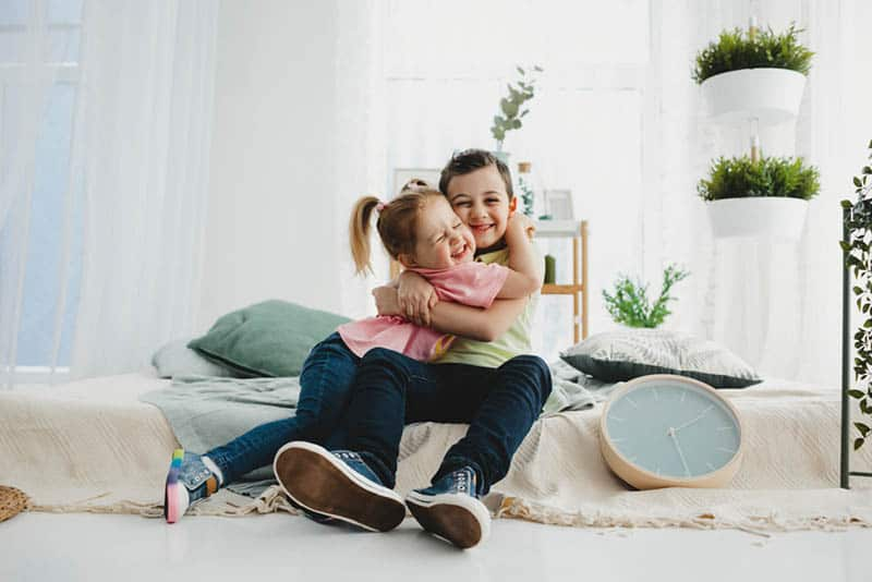 adorable little girl hugging with her brother on the couch