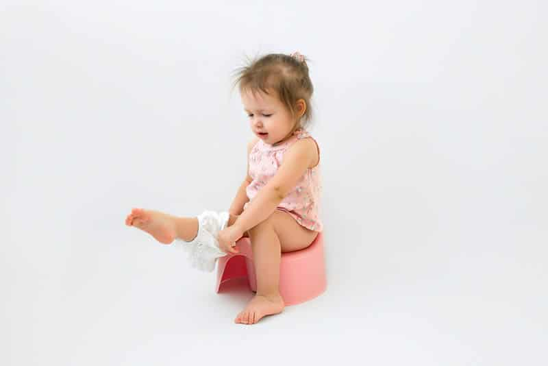 adorable little girl sitting on a potty with panties on leg