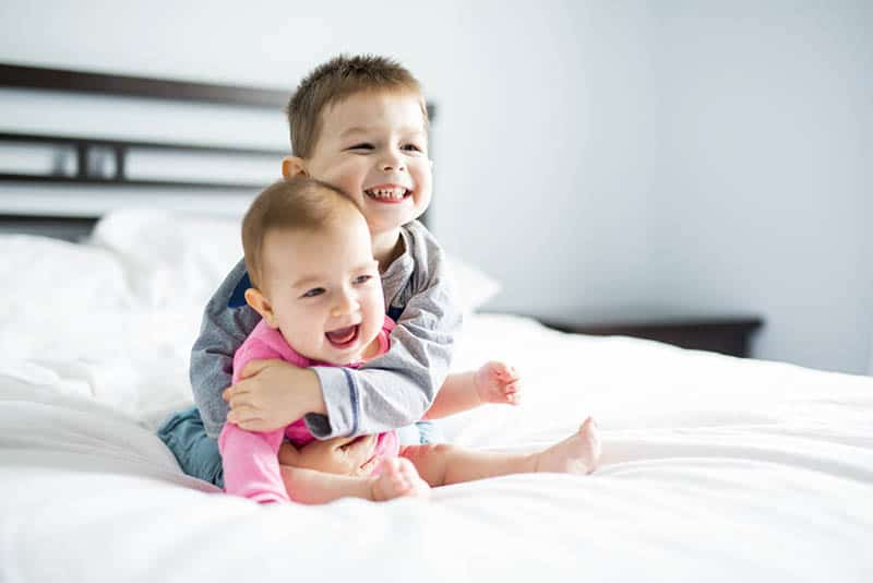 adorable little kid hugging his baby sister on the bed