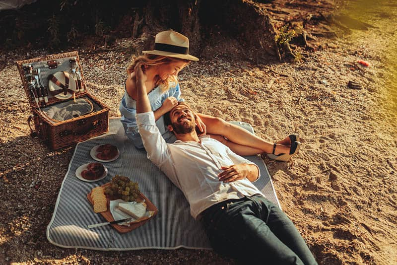 beautiful young couple cuddling on picnic in nature