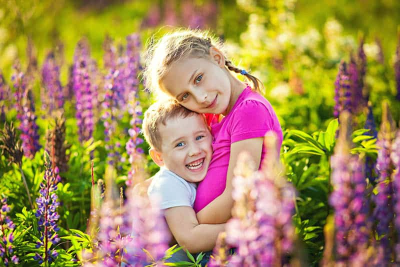 big sister hugging her brother in the lavender field