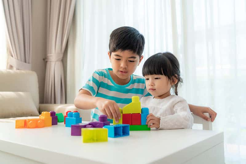 brother and sister playing with cubes on the table at home