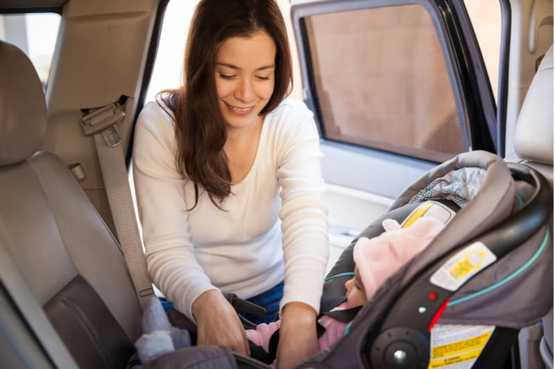 brunette fastening the seat belt of a child car seat before going for a ride