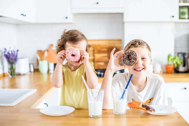 children having fun with donuts for breakfast at home
