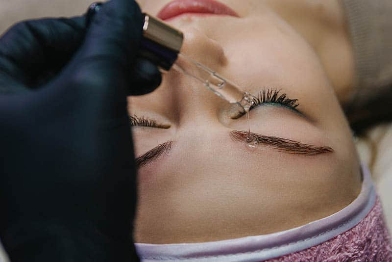 cosmetologist using liquid on woman's eyebrow after microblading