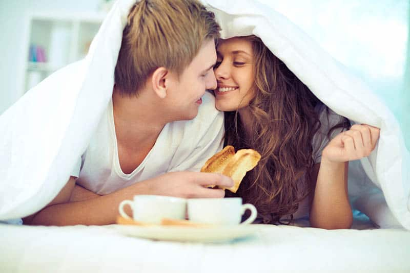 couple cuddling in the bed with morning breakfast