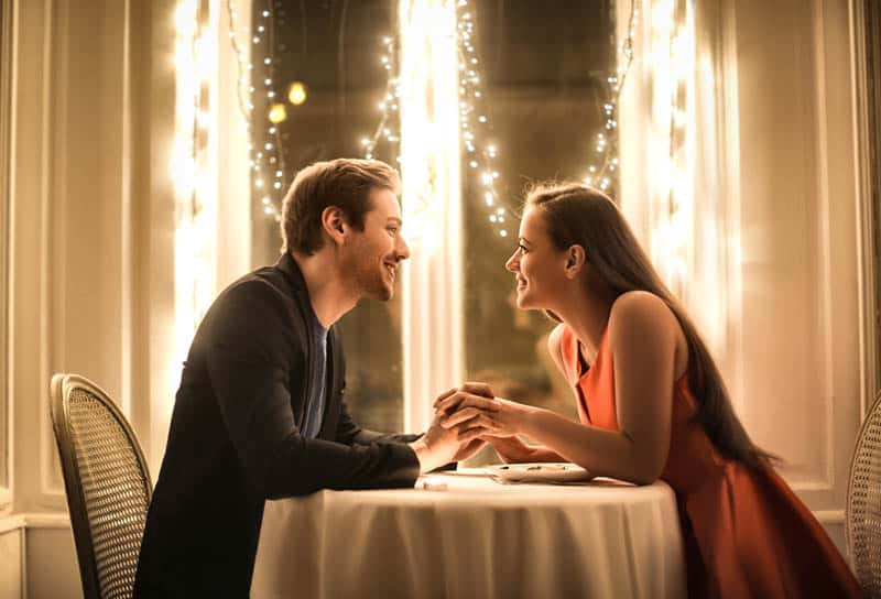 couple in love holding hands in restaurant