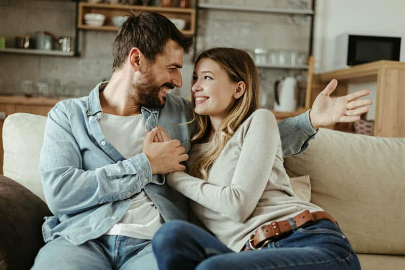 couple in love sitting on the couch and smiling