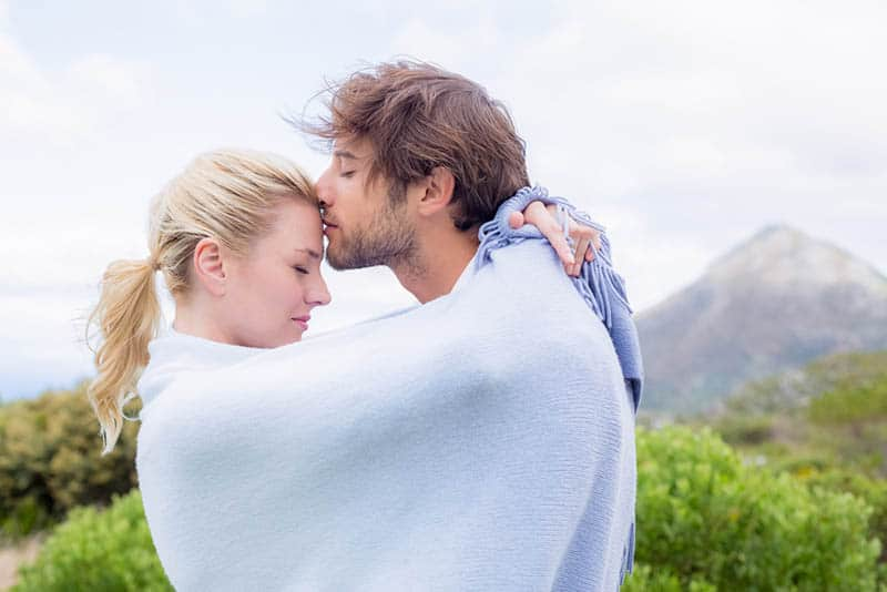couple in love wrapped into blanket kissing outdoor