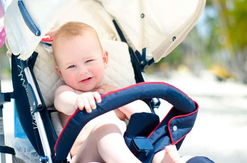 cute baby boy sitting in a stroller on the beach