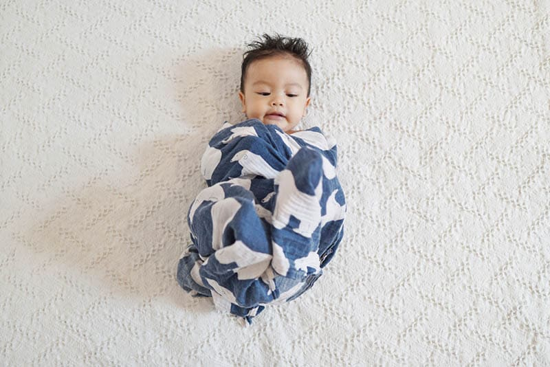 cute baby boy trying to take of the swaddle cloth