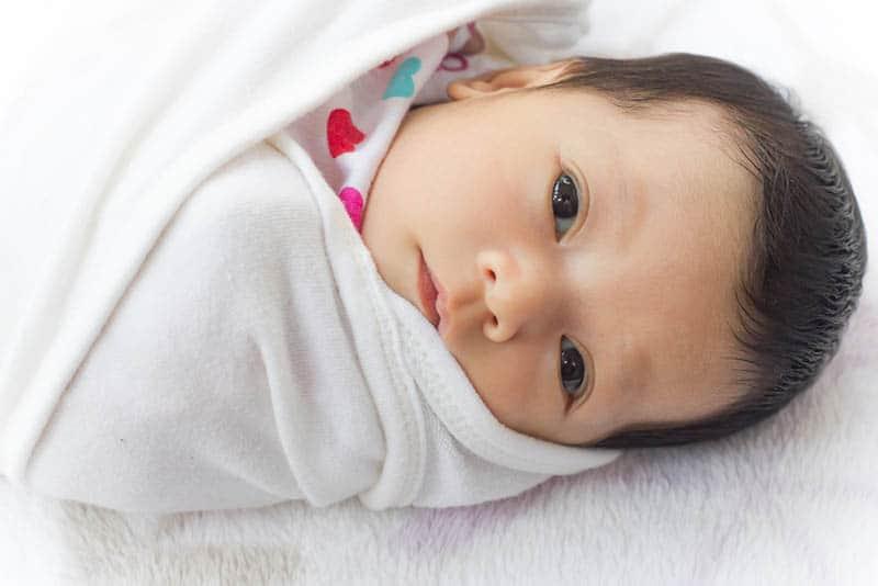 cute baby lying still swaddled in white blanket