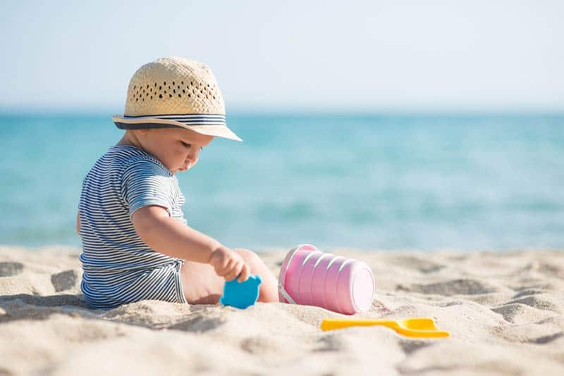 cute baby with hat playing in the sand on the beach