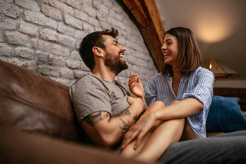 cute couple laughing on the couch at home