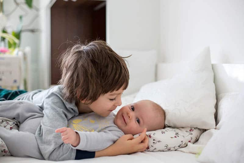cute little boy cuddling with his baby brother on the bed