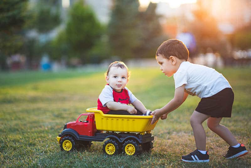 cute little boy playing with brother in a truck toy outdoor