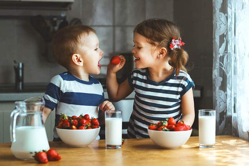 cute little girl feeding her brother with strawberry in the kitchen