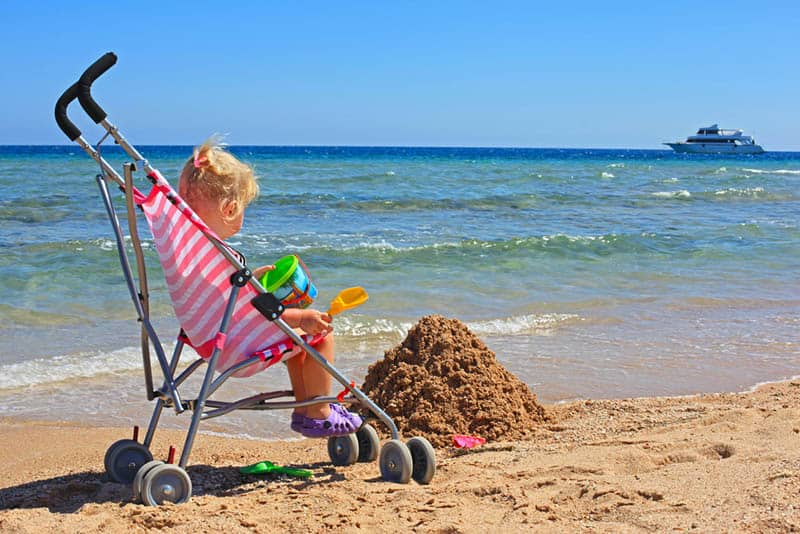 cute little girl playing in a stroller on the beach